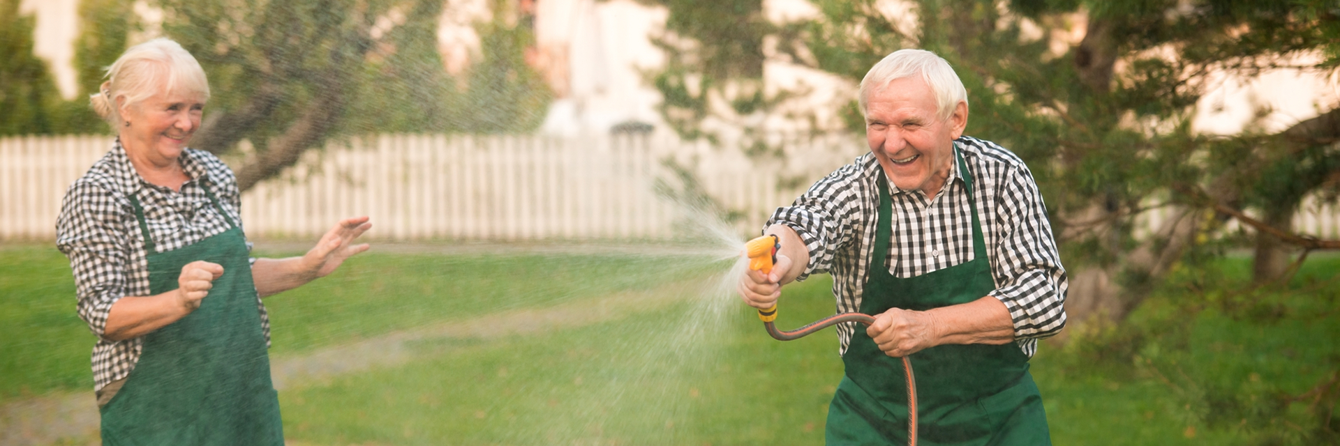 Happy Senior Couple having fun with water hose